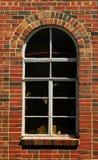 välvt tegelstenväggfönster Arkivbild