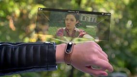 Vän för appell för flickaidrottsmanhand som syns i hologram Teknologisk smart klocka som är futuristisk och gröna träd in stock video