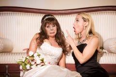 Vän som drar skam över den olyckliga bruden som sitter på golv arkivfoto