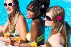 Vän som dricker coctailar i simbassängstång Royaltyfri Foto