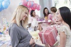 Vän som ger gåvan till gravida kvinnan royaltyfri fotografi