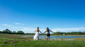 Vänblondin & brunett för två kvinnor med långa hårinnehavhänder i ett fält bredvid en sjö i florida arkivfoto