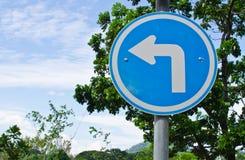 Vänd för trafiktecken som lämnas i parkera Royaltyfria Foton
