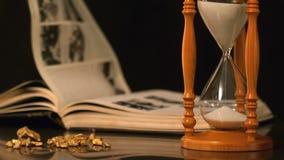 Vända för sidor i vinden bredvid timglaset och guld- klumpar
