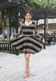 Vända mot av asiatisk kvinna i tappningklänning utformar Arkivfoto