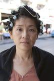 Vända mot av rullande hårkrullning för asiatisk kvinna Arkivbild