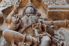 Vända mot bröstet av den kvinnliga hinduiska guden på den gamla skulpturväggen Lättnad av den 12th århundradeHoysaleshwara temple Royaltyfri Foto