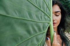 Vända mot den attraktiva unga kvinnan mot ett tropiskt träd för stort grönt blad royaltyfri foto
