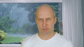 Vända mot den ilskna mannen som in camera ser på bakgrundssikt från fönster på tropiskt regn lager videofilmer