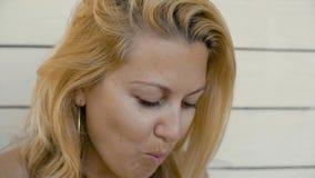 Vända mot den lyckliga kvinnan som biter upp och tuggar rött jordgubbeslut arkivfilmer