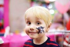 Vända mot målning för gullig pys under ungefödelsedagpartiet Royaltyfria Foton