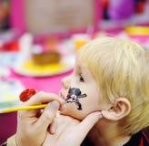 Vända mot målning för gullig pys under ungefödelsedagpartiet Arkivfoto