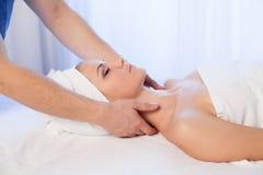 Vända mot och hångla den härliga kvinnan för massagen på Spa royaltyfri bild
