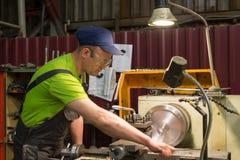 Vändande arbeten Drejaren gör en metalldel på en mekanisk drejbänk Arkivfoto