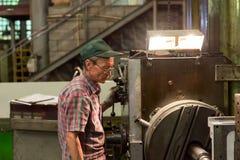 Vändande arbeten Drejaren gör en metalldel på en mekanisk drejbänk Arkivfoton