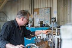 Vändande arbeten Drejaren gör en metalldel på en mekanisk drejbänk Royaltyfri Foto