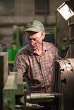 Vändande arbeten Drejaren gör en metalldel på en mekanisk drejbänk Royaltyfri Bild