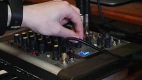 Vändande knoppar för hand och skjutande knappar på studio för bräde för musikljud blandande hemmastadd anteckna nära övre sikt av lager videofilmer