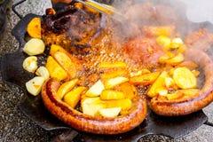 Vändande läcker potatis och saftiga korvar på grillfestplattan med handtaget arkivfoton
