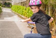 Vänder den bärande hjälmen för ung flickaridningcykeln hennes huvud och blick Royaltyfri Bild
