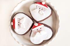 Vänder mot små kakor formade Santa Claus Arkivbild