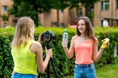 vänflicka två Sommar i natur Rekord- video på kamera Begreppet av unga bloggers äta som är sunt Sinnesrörelser är royaltyfri fotografi