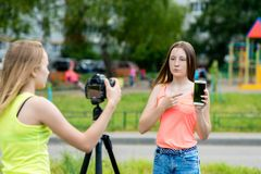 vänflicka två Sommar i natur Rekord- video på kameran I hans händer rymmer en smartphone Begreppet av barn royaltyfri foto
