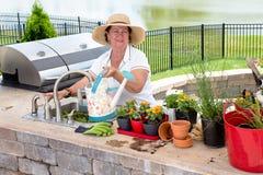 Vänlig äldre dam som bevattnar hennes houseplants Arkivfoton