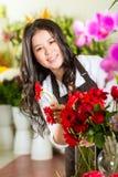 Kinesisk Saleswoman i en blomsterhandel Arkivfoto