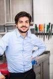 Vänlig attraktiv man i ett kommersiellt kök Arkivfoto
