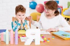 Vänlig barnterapeut som försöker att nå pojkens mening arkivfoton