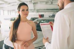 Vänlig bilförsäljare som talar till en ung kvinna och visar en ny bil inom visningslokalunderteckning av avtalet fotografering för bildbyråer