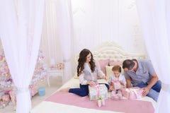 Vänlig familj i det festliga lynnet som utbyter gåvor som sitter på säng Arkivfoto