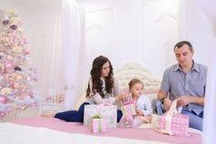 Vänlig familj i det festliga lynnet som utbyter gåvor som sitter på säng Arkivfoton