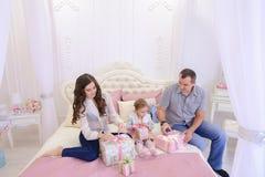 Vänlig familj i det festliga lynnet som utbyter gåvor som sitter på säng Royaltyfria Foton
