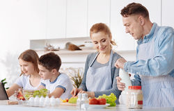Vänlig familj som tillsammans lagar mat i köket fotografering för bildbyråer