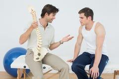 Vänlig fysioterapeut som förklarar ryggen till en patient royaltyfri fotografi