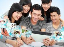 Vänlig grupp av studenter med minnestavlaPC arkivfoton