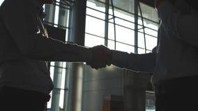 Vänlig handskakning av två affärsmän som hälsar sig i kontoret Inomhus affärshandskakning Skaka av manliga armar arkivfilmer