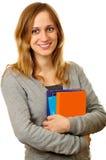 Vänlig kvinnlig deltagare med böcker Royaltyfri Foto