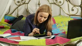 Vänlig läsning för kvinnlig student på den digitala minnestavlan som ligger i säng On-line utbildning för härlig kvinna i hem lån arkivfilmer
