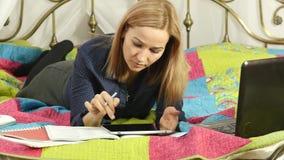 Vänlig läsning för kvinnlig student på den digitala minnestavlan som ligger i säng On-line utbildning för härlig kvinna i hem 4K lager videofilmer