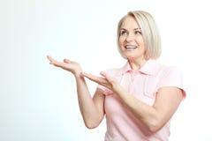 Vänlig le mitt åldras kvinna som pekar på isolerad copyspace Royaltyfria Bilder