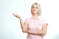 Vänlig le mitt åldras kvinna som pekar på isolerad copyspace Arkivfoton
