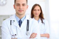 Vänlig manlig doktor på bakgrunden av den kvinnliga läkaren i sjukhuskontor arkivfoto