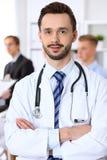 Vänlig manlig doktor på bakgrundsdoktorn och många patienter Arkivbilder