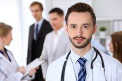 Vänlig manlig doktor på bakgrundsdoktorn och många patienter Royaltyfria Foton