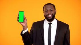 V?nlig stilig afro--amerikan man i dr?kten som visar den prekeyed telefonen, mall royaltyfria bilder