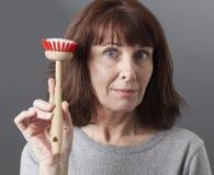 Vänlig 50-talkvinna som räcker över ansvar för att göra ren disk Royaltyfri Foto