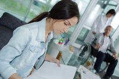 Vänlig ung kvinna bak administratör för mottagandeskrivbord arkivfoton
